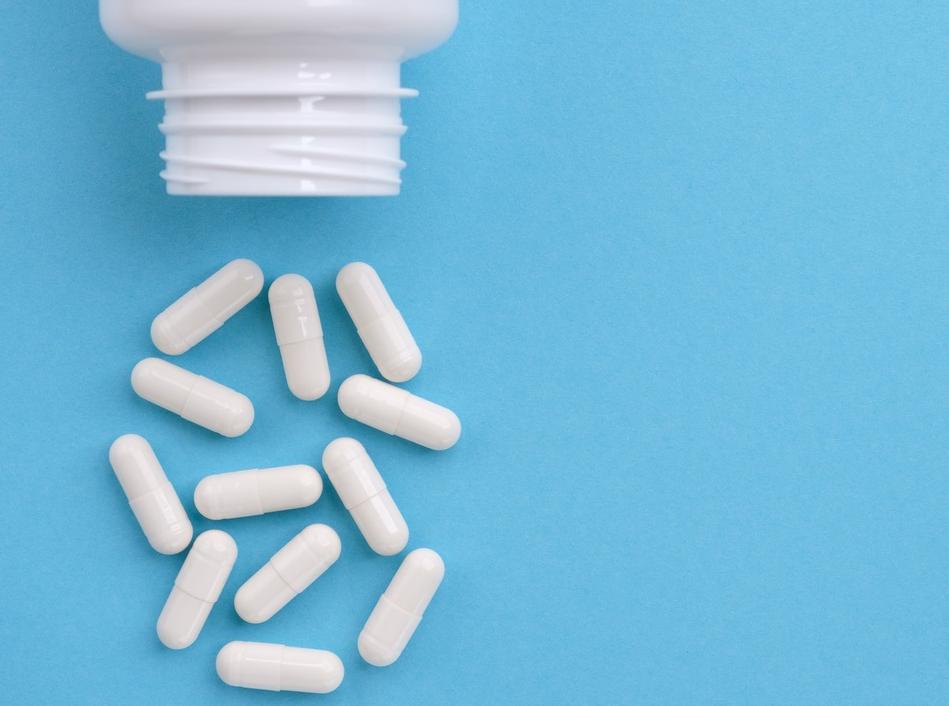White medication capsules spilling from bottle