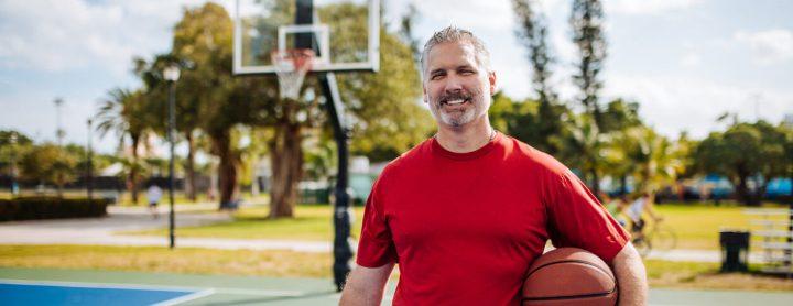 Man holding basketball on basketball court