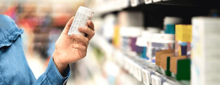 Customer in pharmacy holding medicine bottle