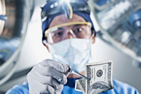 Hernia mesh surgeon holding money