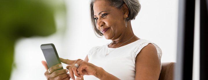 Woman smiling at phone screen