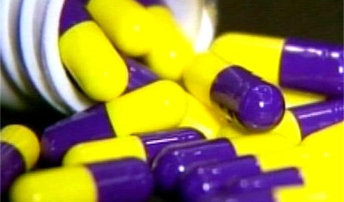 yellow and purple pills spilling out of a bottle