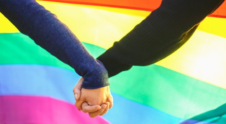 Couple holding hands in front of the Pride flag