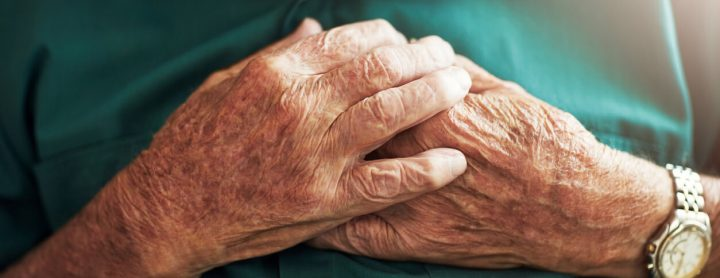 Elderly man in pain with his hands on his chest