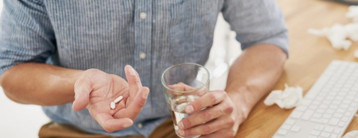 Man taking his medication with water