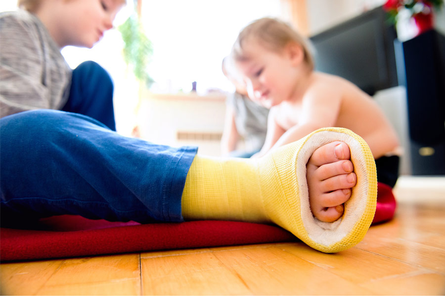 Boy with broken leg with his brother playing