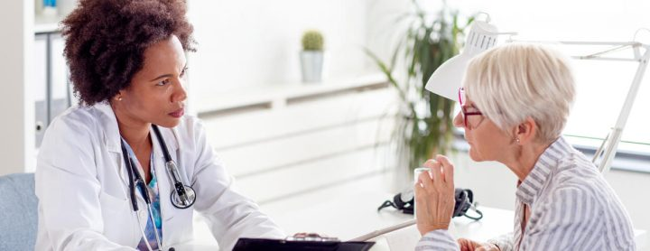 Woman speaking with doctor at her desk