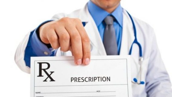 doctor holding up a prescription sheet