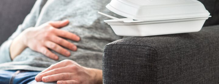 Man with stomach pain on couch sitting next to takeout box