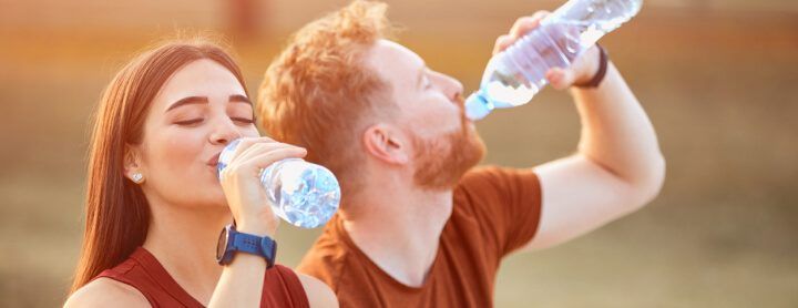 Woman and man drinking water on a run
