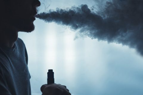 A bearded man vaping with a cloud of smoke