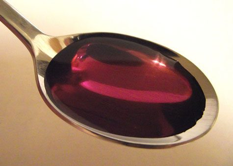 Purple cough syrup in spoon