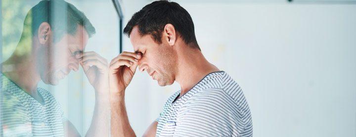 Man with a headache by a window