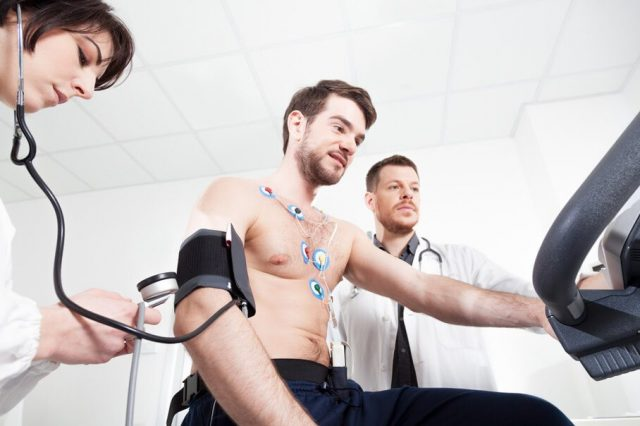Doctors monitoring a male patient on exercise bike