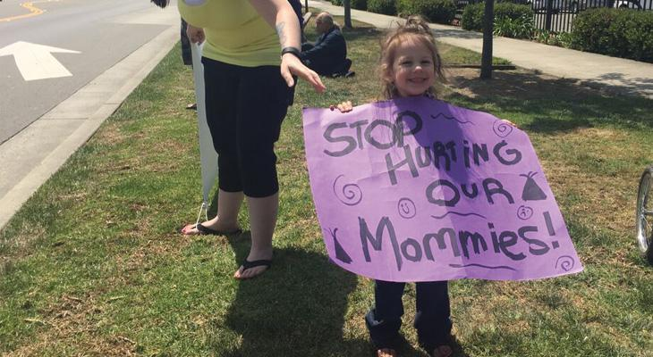 little girl holding a protest sign