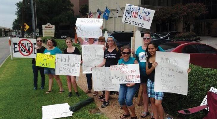 women hold anti-Essure signs
