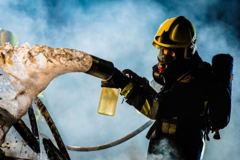 Firefighter extinguishing car fire with foam spray