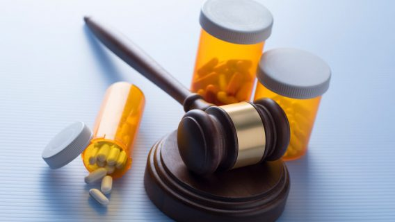 Bottles of medicine with a judge's gavel
