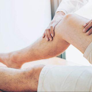 Doctor examines man's leg