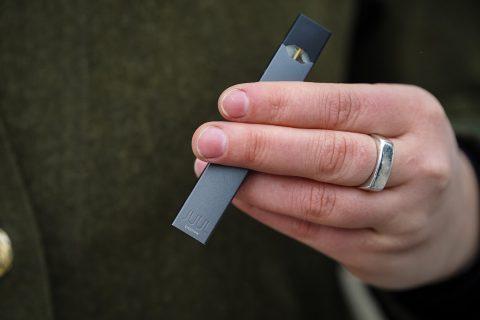 Hand holding a JUUL e-cigarette