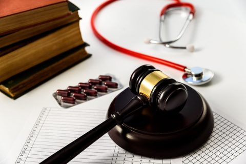 Judge gavel with pills and stethoscope