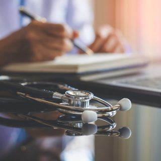 Doctor writing with a stethoscope on desk