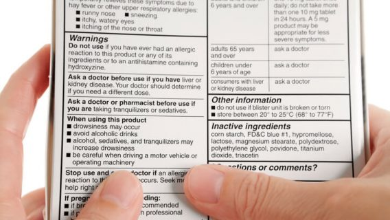 Person reading drug label on back of box