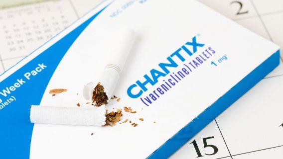 Broken cigarette on top of a pack of Chantix pills