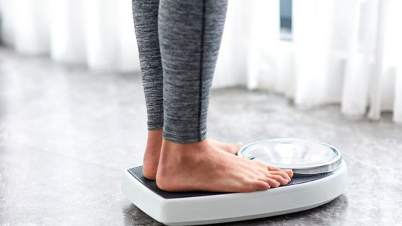 Person weighing themselves on a scale
