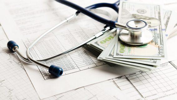 Dollar bills next to stethoscope