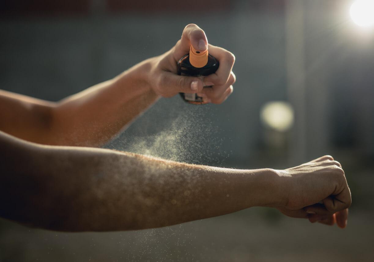 Woman spraying aerosol sunscreen on her arm