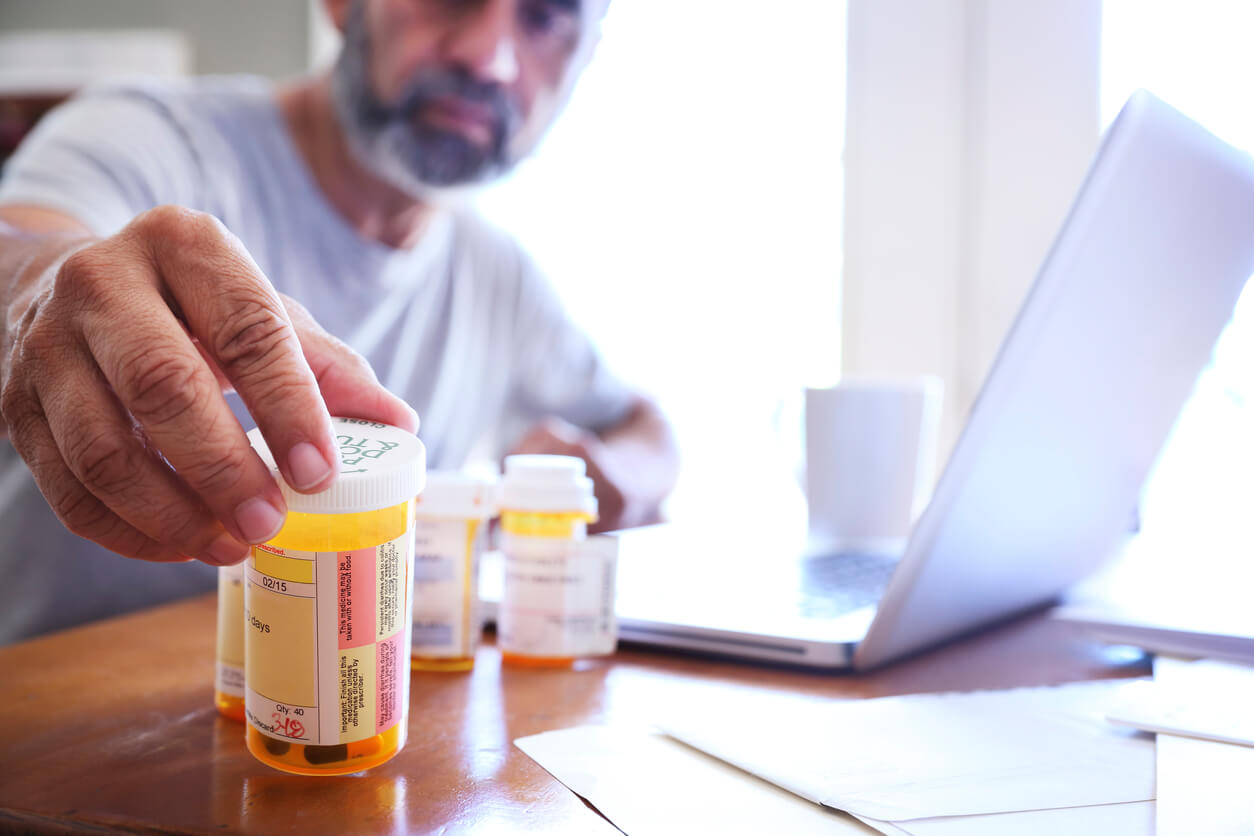 Man looking at a pill bottle