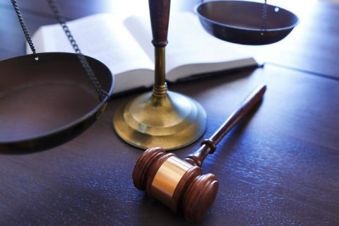 Gavel and scale on wooden desk
