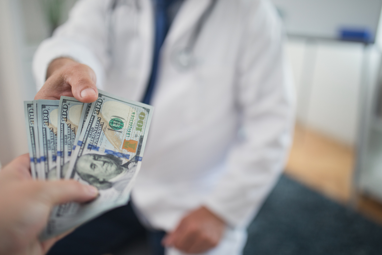 Doctor receiving cash from individual