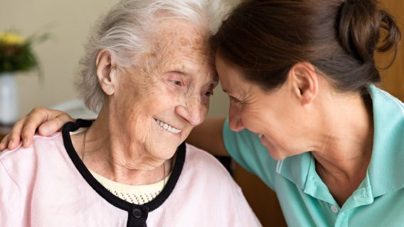 Caregiver and senior woman embracing