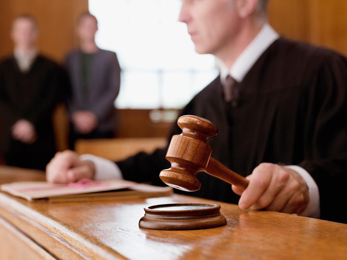 Judge holding gavel in court room