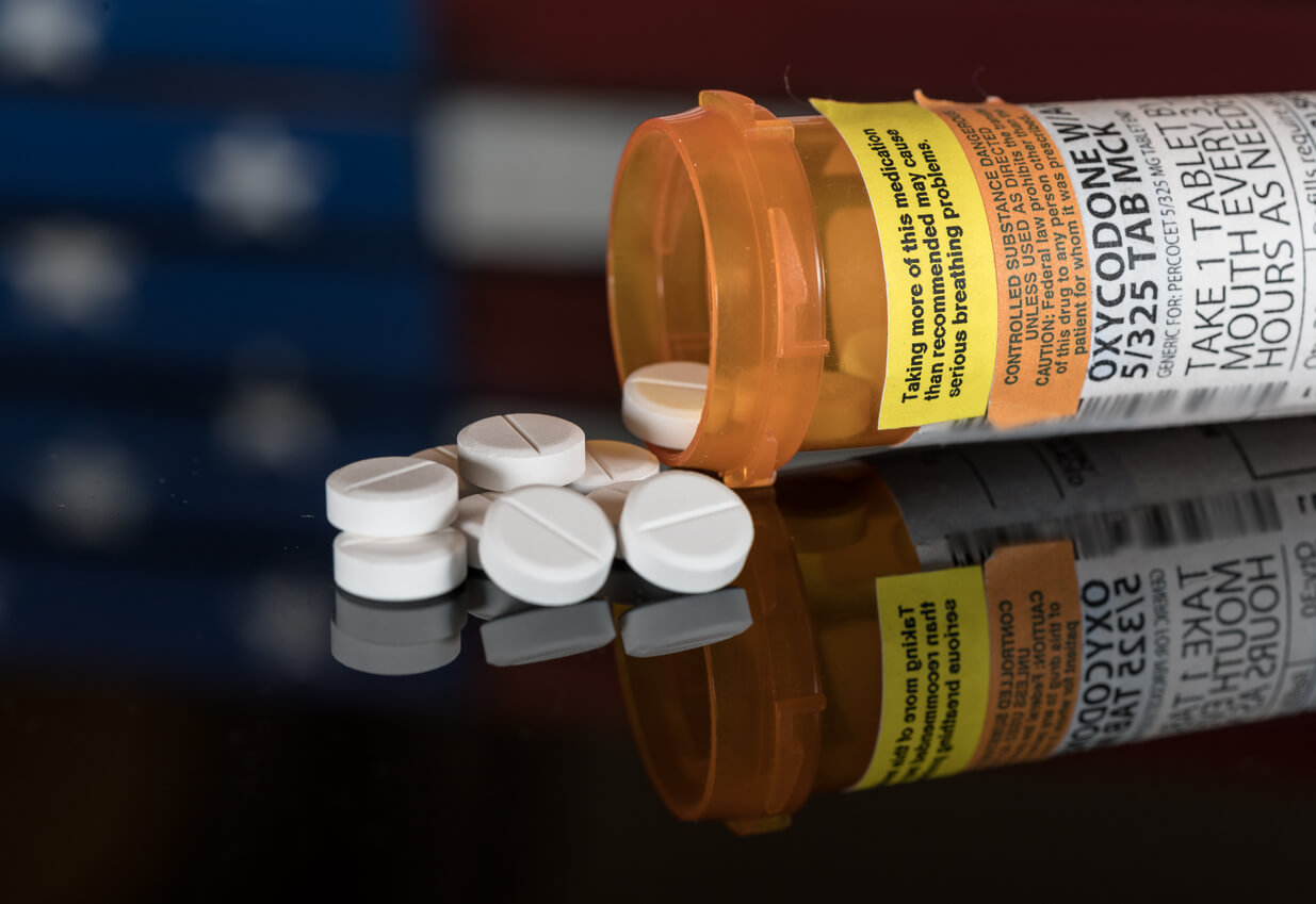 Oxycodone pills with American flag in background
