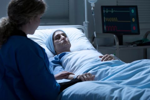 woman in coma with relative by her side