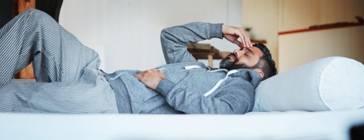 Man lying down in bed while in pain