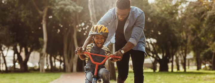 Man teaching his son how to ride a bike