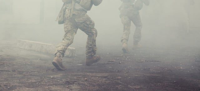 Army soldiers running in smoke during combat