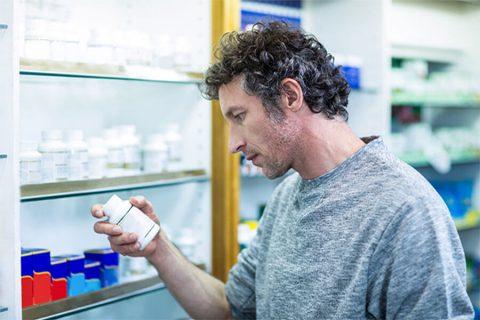 man reading a pill bottle in a pharmacy