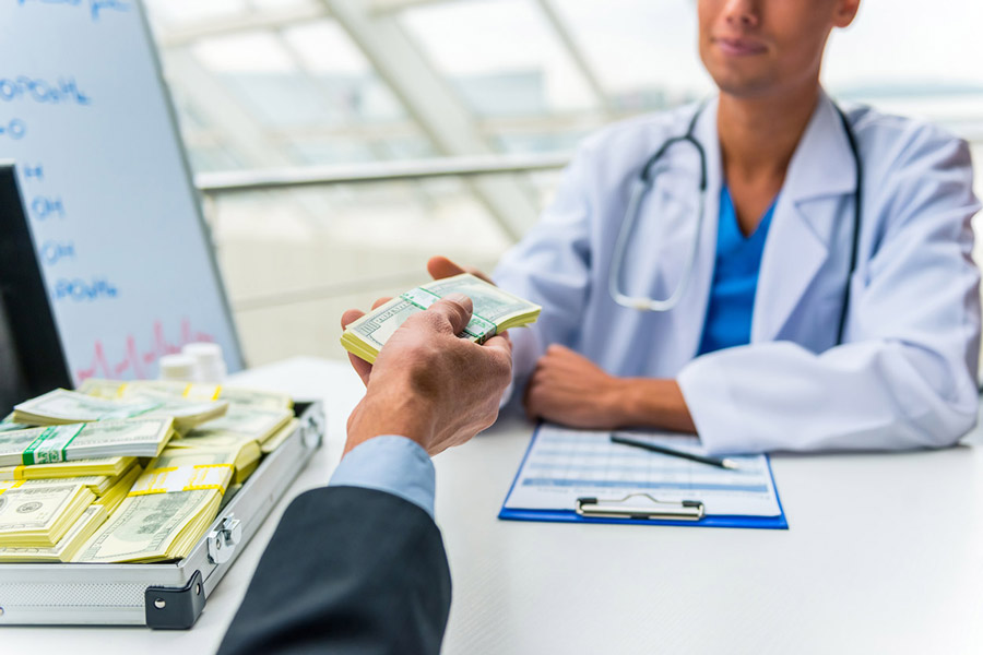 businessman bribing doctor with a suitcase full of money