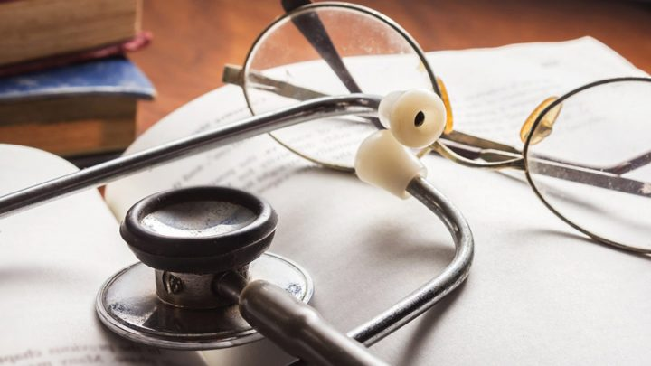 stethoscope and glasses resting on a book