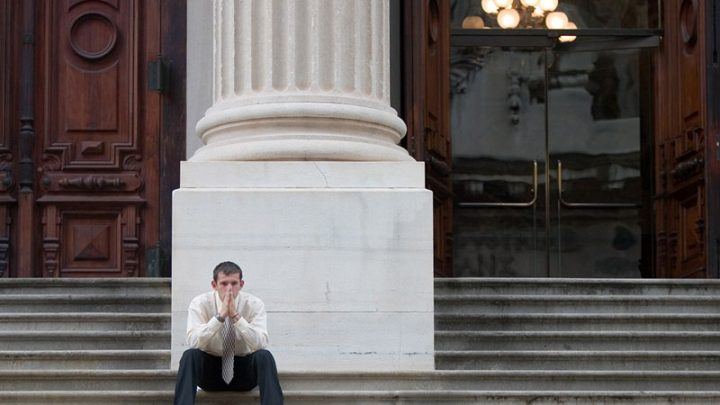 Upset man setting on steps of courthouse