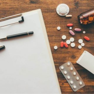 clipboard and pills on top of a table