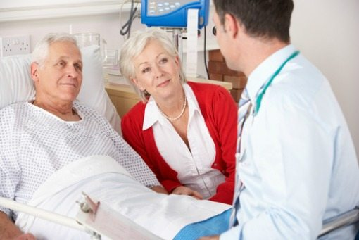 doctor visiting elderly man in his hospital room and his wife