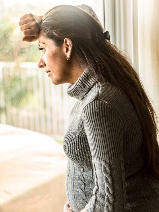 concerned pregnant woman looking out window