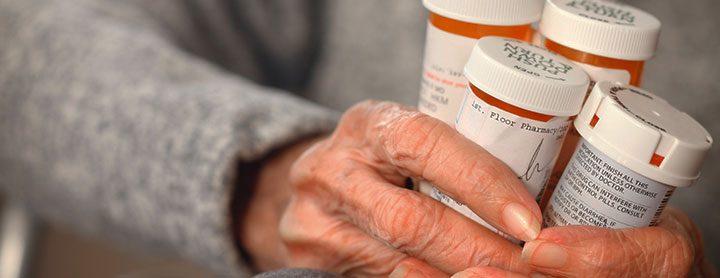 older woman holding a variety of prescription bottles