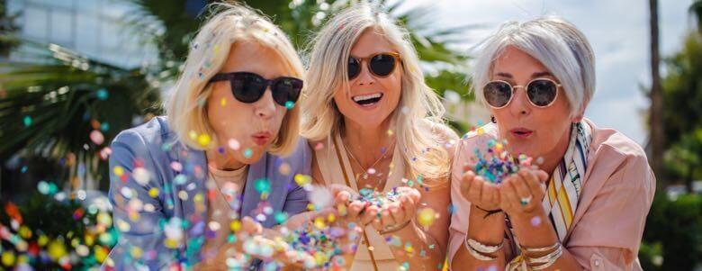 elderly ladies blowing confetti